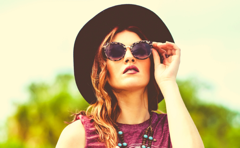Young woman wearing hat and turquoise necklace looking at sun through leopard print sunglasses