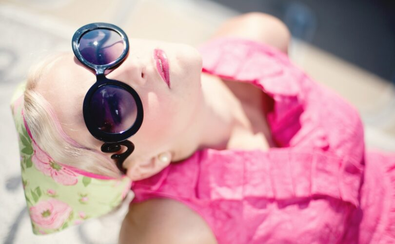Blond woman wearing dark sunglasses and pink shirt