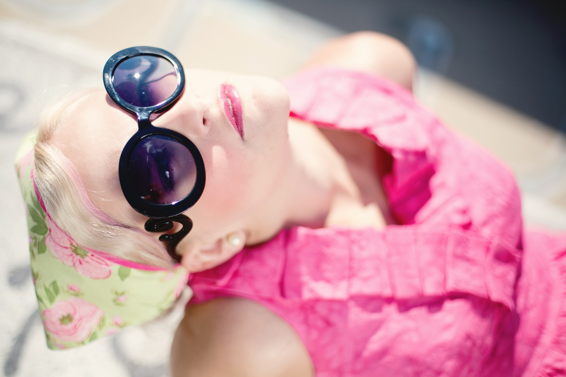 Blond woman wearing dark sunglasses and pink shirt
